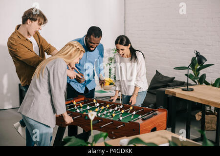 businesswomen playing table football and two male colleagues pointing on board game - Stock Photo
