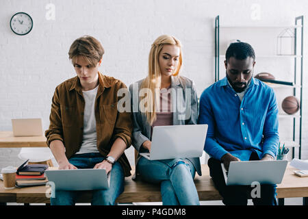 three multicultural business colleagues using laptops and sitting on table in modern office - Stock Photo