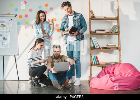 Successful business people sharing ideas in modern light office - Stock Photo
