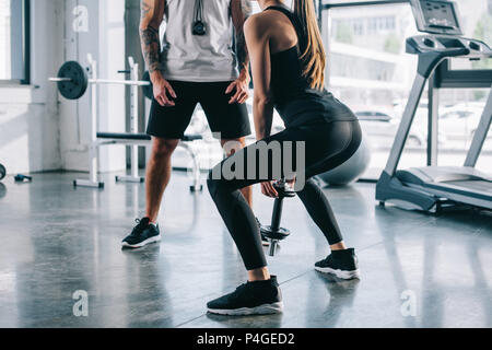 sportswoman doing exercises with dumbbell and male personal trainer standing near at gym - Stock Photo
