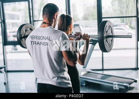 male personal trainer helping sportswoman to do exercises with barbell at gym - Stock Photo