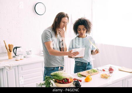 multicultural young couple looking at recipe on digital tablet and cooking at kitchen - Stock Photo