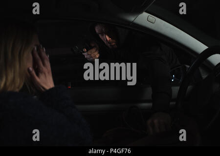 male thief aiming by gun and stealing bag from woman sitting in car - Stock Photo
