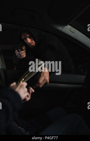 serious male thief aiming by gun and stealing bag from woman sitting in car - Stock Photo