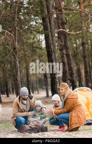 beautiful young family making campfire in autumn forest - Stock Photo