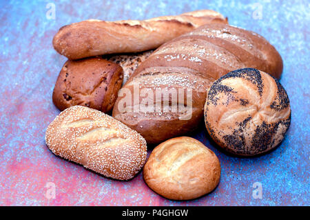 Golden Bread variety , rolls and loaves;  Salted rye, french baguette, onion roll, poppy seed, sesame seed, and plain roll - Stock Photo