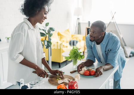 african american man looking at wife cooking breakfast in kitchen at home - Stock Photo
