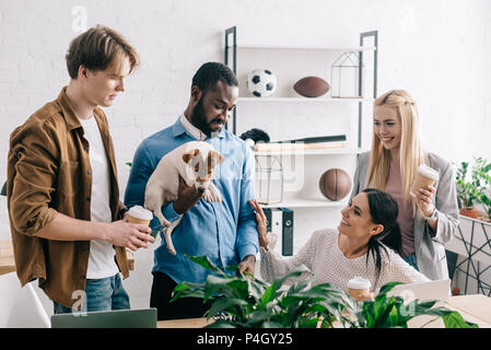 african american businessman holding jack russell terrier and smiling colleagues standing near - Stock Photo