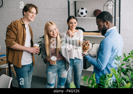 african american businessman holding dog surrounded by smiling colleagues with coffee cups - Stock Photo