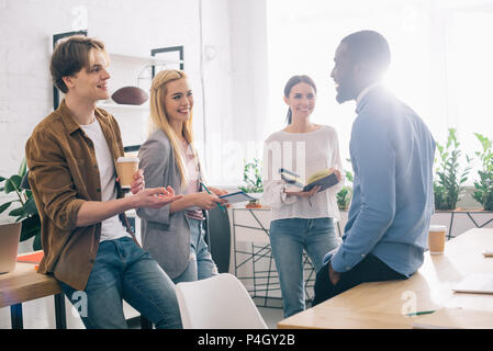 multicultural businesspeople with coffee and textbooks having meeting in modern office - Stock Photo