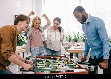 side view of happy multicultural businessmen playing table football in front of celebrating and gesturing female colleagues - Stock Photo