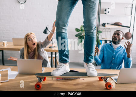 cropped image of businessman riding on longboard on table and shocked colleagues in modern office - Stock Photo