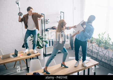 high angle view of multiethnic two colleagues fighting on table in modern office - Stock Photo