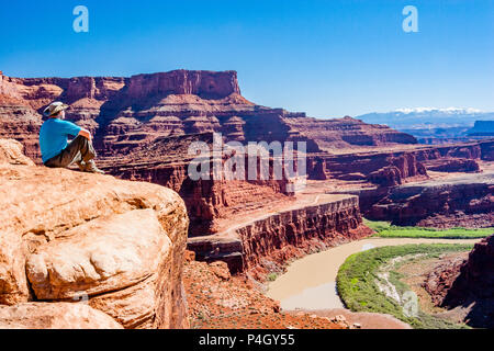From Goosenecks overlook along the White Rim Road, a Man views Colorado River Goose neck area, Shafer Trail, sandstone cliffs and distant mountains. - Stock Photo