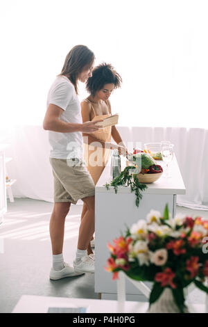 side view of multicultural couple with recipe in book cooking at kitchen - Stock Photo
