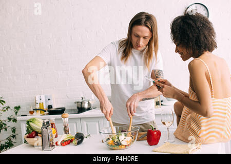 side view of smiling african american woman shooting preparing of salad by her boyfriend - Stock Photo