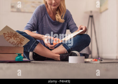 cropped shot of smiling blonde woman paper crafting at home - Stock Photo
