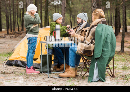 beautiful young family on camping in forest - Stock Photo