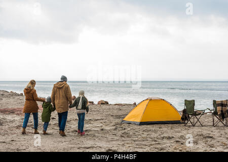 young family holding hands and walking to tent on seashore - Stock Photo