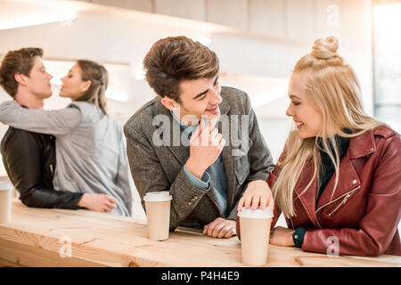 One heterosexual couple kissing, another couple talking at the wooden bar counter - Stock Photo