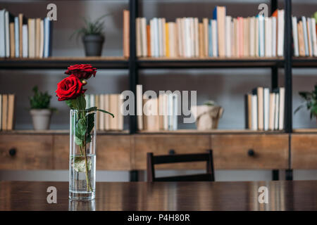 beautiful red roses in vase at library - Stock Photo