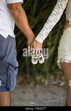 Detail of parents holding golden girl shoes, seen from behind. - Stock Photo