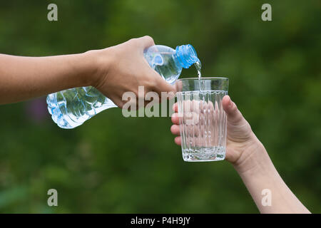 hand pouring clean water from bottle into glass on nature background - Stock Photo