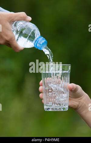 hand pouring water from bottle into glass on nature background - Stock Photo