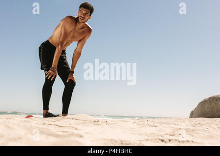Man doing fitness workout at a beach. Man taking rest during workout with hands resting on knees standing at the beach. - Stock Photo