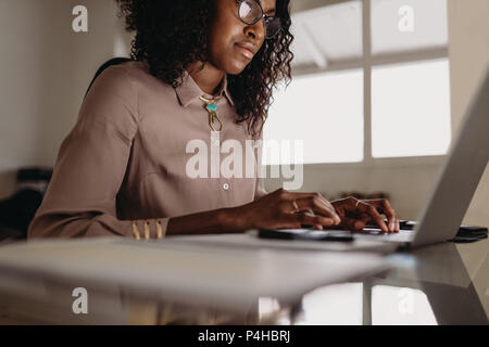 Businesswoman working on laptop computer from home. Woman entrepreneur sitting at home working on laptop with business documents on the table.