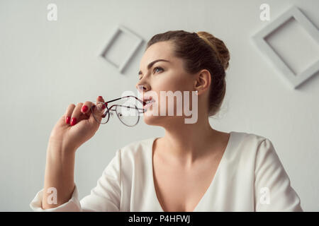 portrait of pensive attractive blonde businesswoman with eyeglasses in modern office - Stock Photo