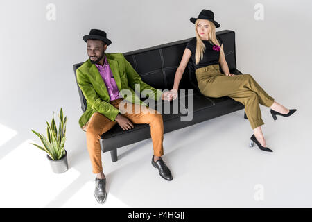 multicultural fashionable couple in hats holding hands on black sofa on grey backdrop - Stock Photo