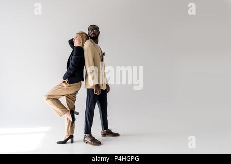 side view of fashionable young multiethnic couple posing back to back on grey - Stock Photo