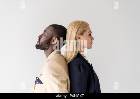 side view of stylish young multiethnic couple standing back to back isolated on grey - Stock Photo