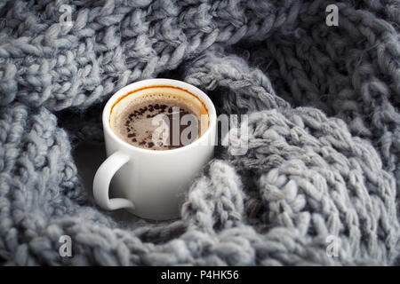 a cup of aromatic coffee wrapped in wool sirloin snod - Stock Photo
