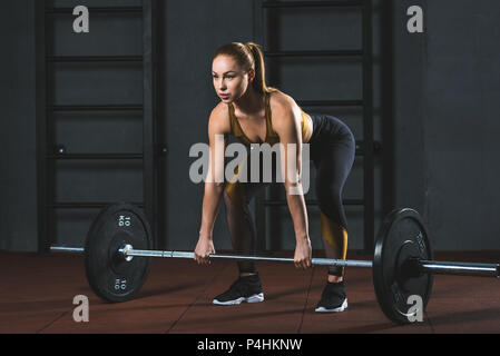 Front view of young sportswoman preparing to raise barbell in sports hall - Stock Photo
