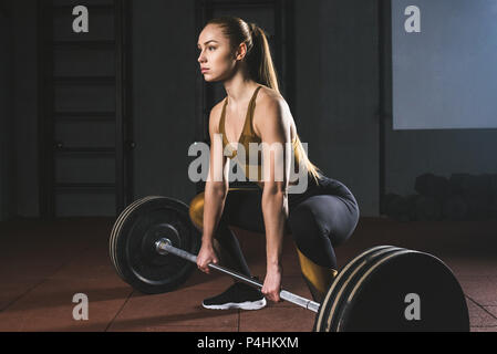 Side view of young sportswoman preparing to raise barbell in gym - Stock Photo