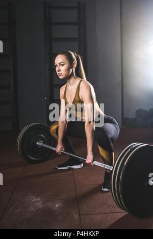 Young sportswoman preparing to raise barbell in gym - Stock Photo
