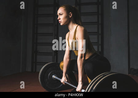 Side view of young bodybuilder preparing to raise barbell in gym - Stock Photo