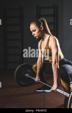 Young female bodybuilder preparing to raise barbell in gym - Stock Photo