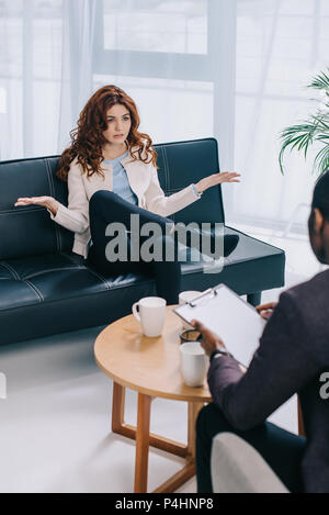Young woman with wide arms talking to psychiatrist - Stock Photo