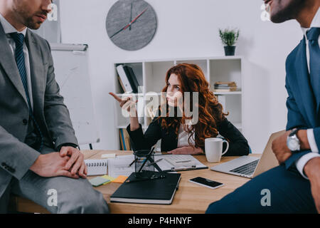 Cropped view of two businessmen sitting on table and manager pointing by finger - Stock Photo