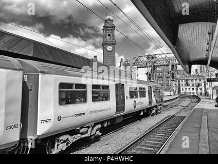 Mono image of Delayed Electric Northern Railway EMU train at Manchester Oxford Road Railway station, North West England, UK, back to the 1970s - Stock Photo
