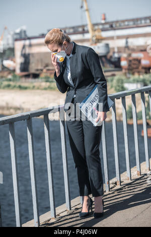 businesswoman touching protective mask on bridge, air pollution concept - Stock Photo