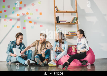 Professional business colleagues men and women sitting on floor and working in modern office - Stock Photo