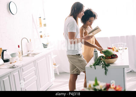 side view of young multiethnic couple cooking and looking at recipe in book - Stock Photo