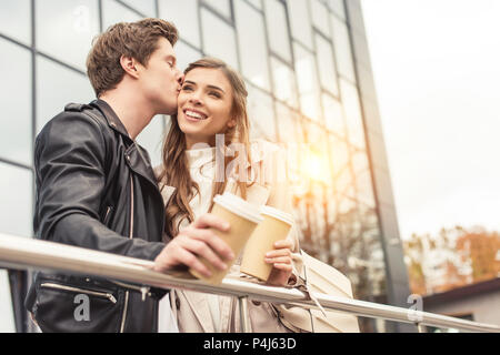 Boyfriend kissing girlfriend standing and leaning on railing - Stock Photo