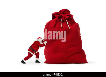 Close up of Santa Claus pushing huge bag of presents isiolated on white background - Stock Photo