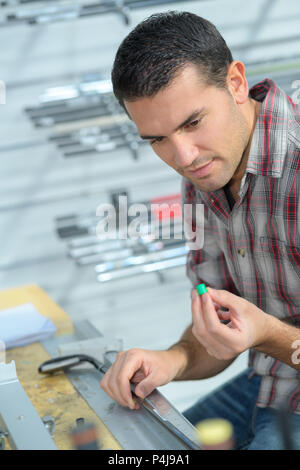 professional worker working on a machine at guitar workshop - Stock Photo