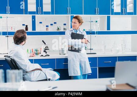 partial view of female scientist in eyeglasses with notepad in hands looking at colleague at workplace in lab - Stock Photo